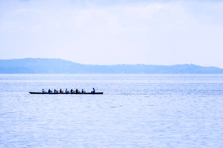 a rowing boat with eight rowers and helmsman seaside Stock Photo