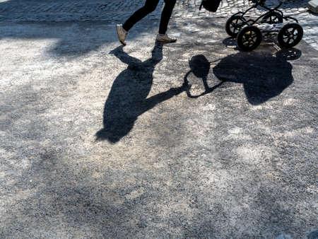 births: shadow eirn woman with a stroller.