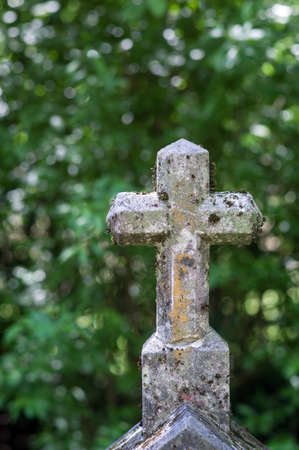 deceased: a stone cross in a cemetery. peace and memory of the deceased.