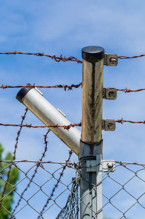 lifelong: a site is secured by a fence with barbed wire Stock Photo