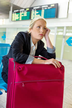 delays: businesswoman waiting for her departure at the airport. symbol photo for delays, flight cancellations and strikes.