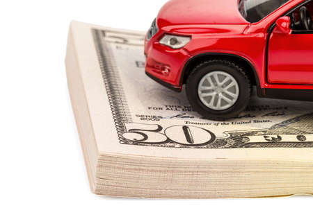 upkeep: a car standing on dollar bills. costs for the purchase of automobiles, gasoline, insurance and other car costs