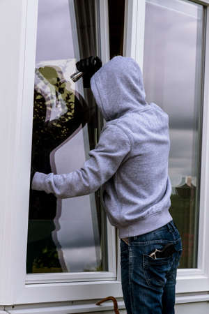 lawbreaker: a burglar attempts at an open window to break in with a crowbar Stock Photo