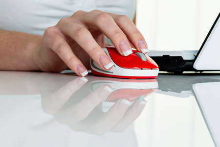 edv: a woman working in an office and h�t the mouse of a computer in hand. Stock Photo
