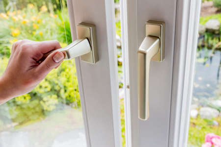 ventana abierta: una mujer abre una ventana para ventilar la vivienda. aire fresco en la habitación