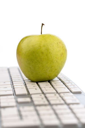 break: an apple is on the keyboard of a computer. symbol photo for healthy and vitamin-rich snack.