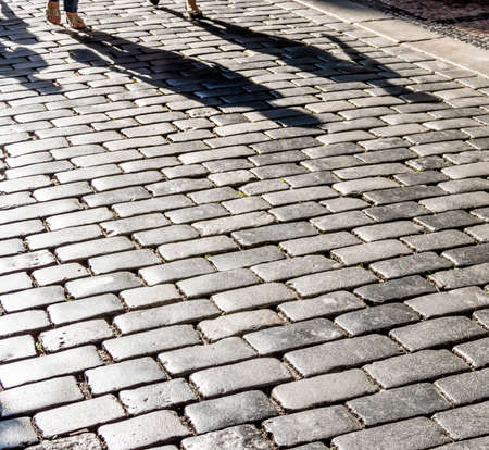 foreigner: shadows of people on a pavement