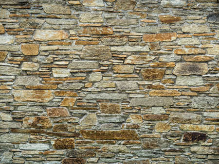 hardness: a stone wall protects from view in a garden. Stock Photo