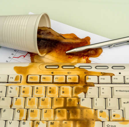 mishap: in an office, a cup spilling coffee on a computer by accident