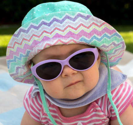 well equipped: a baby with sunglasses and sun hat is well equipped against the heat in summer