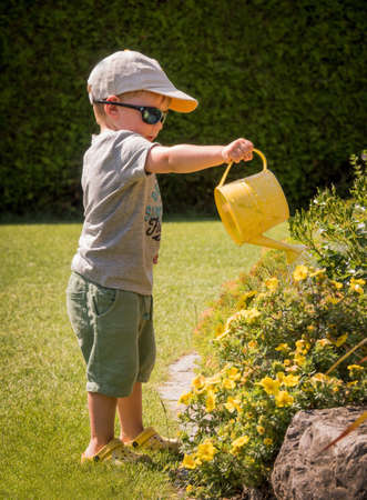 a small boy squirts with a watering the flowers on a hot day in summer