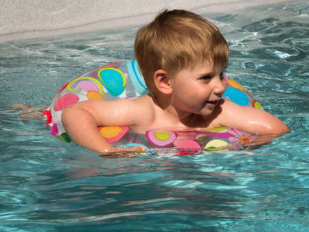paddling: one child swims with a schwimmreifwn in the pool and cooling off on a hot summer day.
