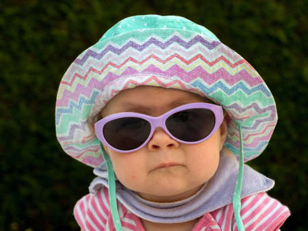 a baby with sunglasses and sun hat is well equipped against the heat in summer