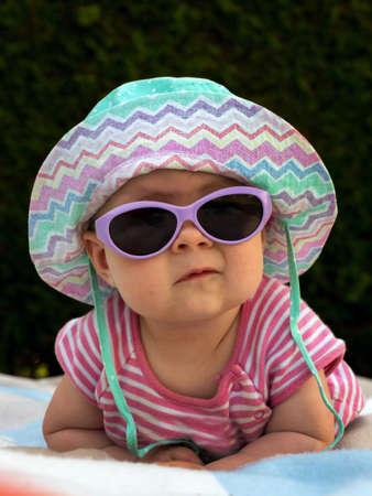 een baby met zonnebril en zonnehoed is goed uitgerust tegen de hitte in de zomer