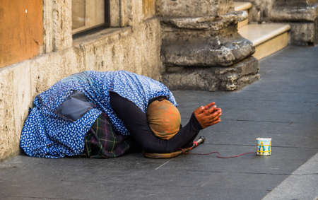 outsider: a beggar on the street. antitheft means red cable Stock Photo