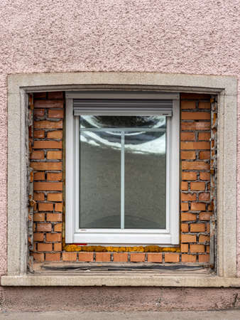 immobilien: in an old residential building a large window was replaced by a new one. symbol for building renovation and housing improvement