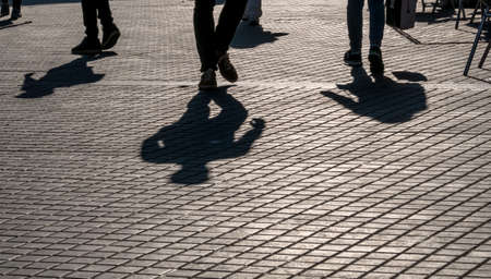 anonym: shadows of passersby on the street plaster Stock Photo
