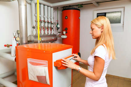 woman at heating in the boiler room Stockfoto