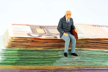 operational: symbol photo for retirement and pension, figure of an old man sitting on a stack of bills