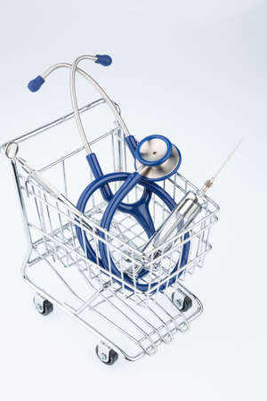 physicans: stethoscope and shopping cart symbol photo for the medical profession and practice acquisition