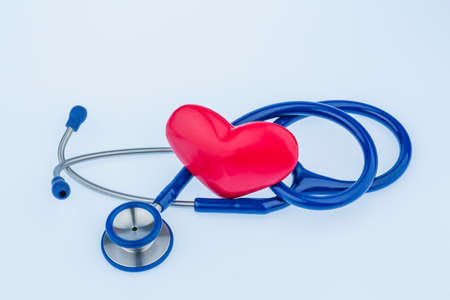 a heart and a stethoscope are adjacent. symbol photo for heart disease and heartache. Stock Photo