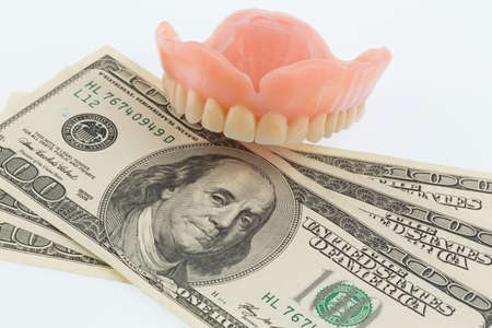 dentures and dollar bills symbol photo for dentures, treatment costs and payment