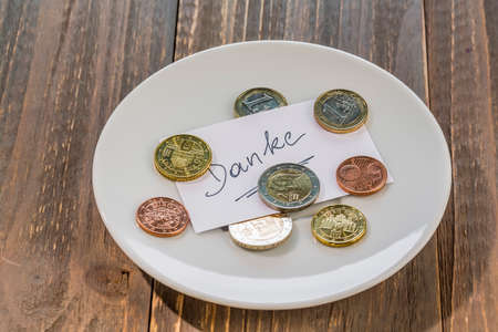 tax tips: a plate of coins for a tip or fee toilets. in german language