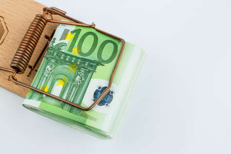 many euro banknotes in a mousetrap. symbol photo for debt and debt on loans.