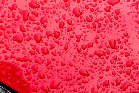 after a rain, droplets of rain onto the paint of a car. drops of water on red background Stock Photo
