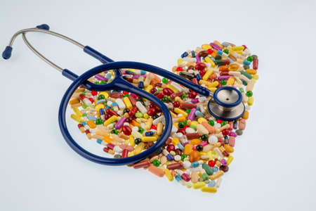 stethoscope and pills in heart-shaped arrangement, symbol photo for heart disease, diagnosis and medication