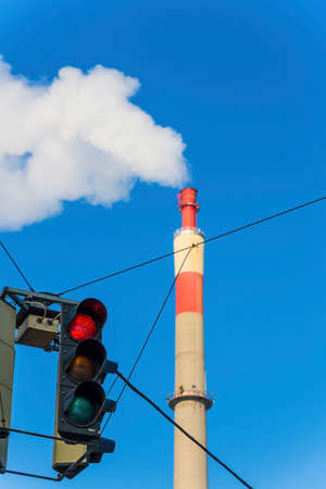 particulate: chimney of an industrial company and a red light. symbol photo for environmental protection and ozone.
