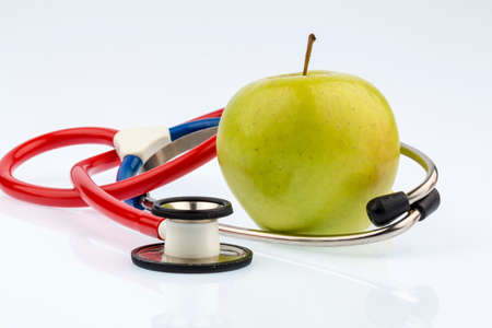an apple and a stethoscope with a doctor. symbol photo for healthy and vitamin-rich diet.