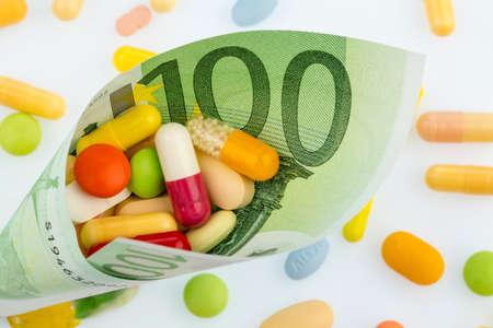 tablets and one hundred euro bill symbol photo: cost of medicine and drugs in the pharmaceutical industry Stock Photo