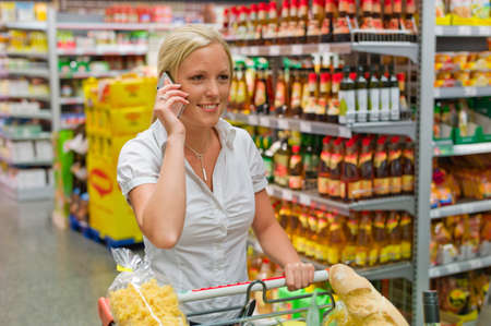 woman with shopping cart in the supermarket Stock Photo