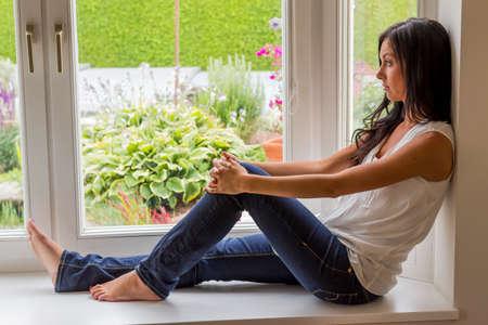 psychologically: woman sitting on window