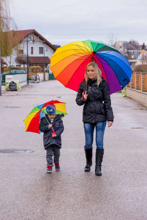 indebtedness: mother and child with umbrella Stock Photo