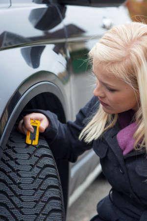 depth measurement: woman measures tire tread of a car tire Stock Photo