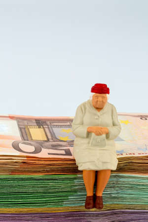 senior sitting on banknotes Stock Photo