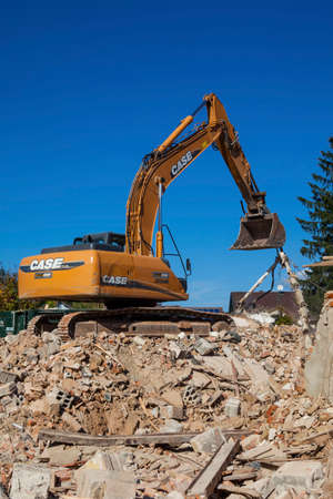 a house is demolished. excavator on the construction site. because of the cancellation of new residential space is created