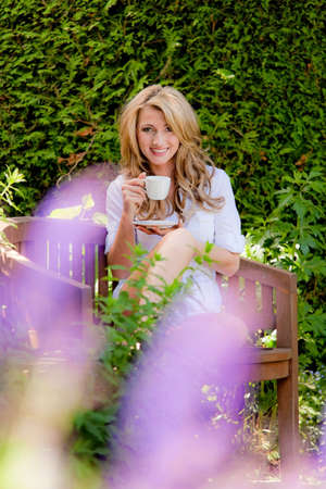 woman drinking coffee at breakfast in the garden photo