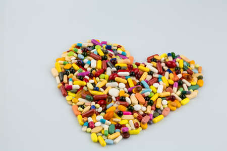 angina: colorful tablets in heart shape Foto de archivo