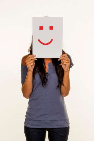 woman holding smiley face before photo