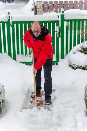 man shoveling while snow