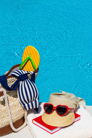 sunhat: utensils for a nice and relaxing holiday lying next to a swimming pool. rest on vacation.