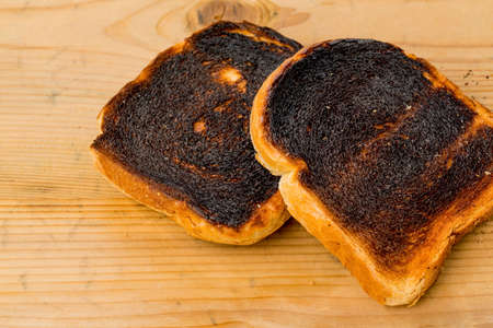 toasted bread was burned while toasting. burnt slices of toast at breakfast. Stock Photo