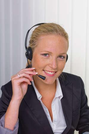 Vriendelijke vrouw met hoofdtelefoon in klantenservice Stockfoto - 89993022