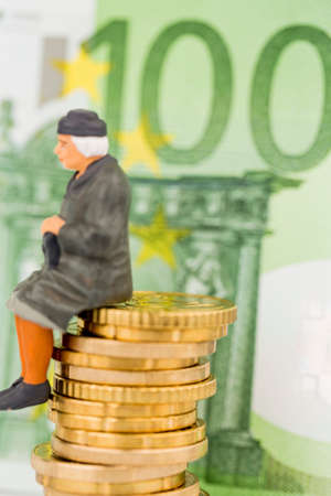 pensioner is sitting on money pile Stock Photo