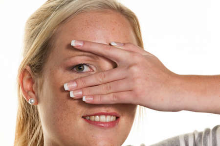 woman looks through fingers of her hand Stock Photo