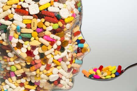 Kopf mit Glas mit Tabletten