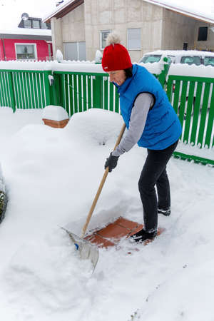 woman shoveling while snow